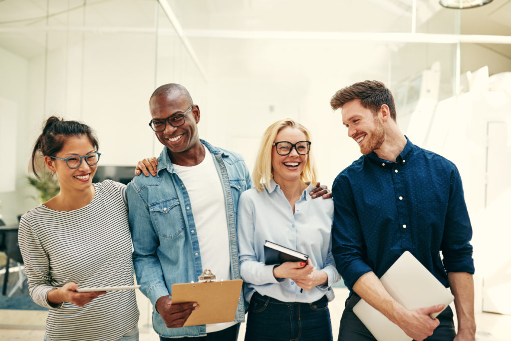 Group of diverse young businesspeople smiling and laughing while standing side by side together in a modern office